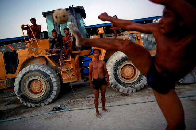 """Workers play """"chinlone"""" after work at a construction site in Yangon, Myanmar on  October 22, 2015. (Photo by Soe Zeya Tun/Reuters)"""