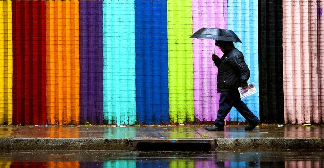 A pedestrian stayed dry walking on Grand Ave. between Spruce St. and Jersey Ave. in Paterson, NJ, on November 17, 2014. (Photo by Amy Newman/The Record of Bergen County)