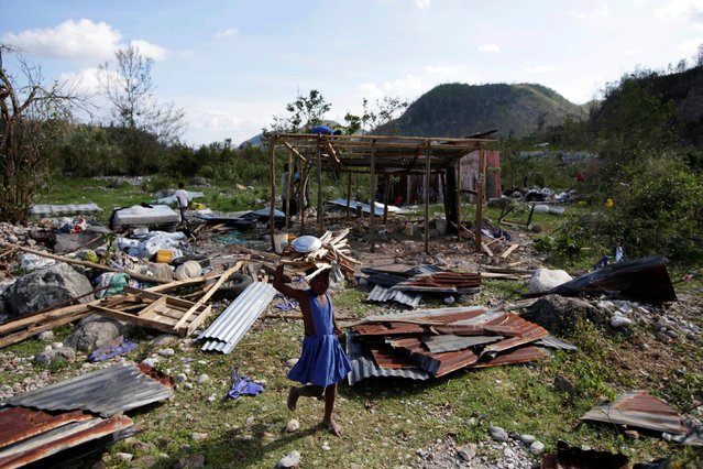 A girl carrying wood walks near debris after Hurricane Matthew passed, in Camp Perrin, Haiti, October 8, 2016. (Photo by Andres Martinez Casares/Reuters)