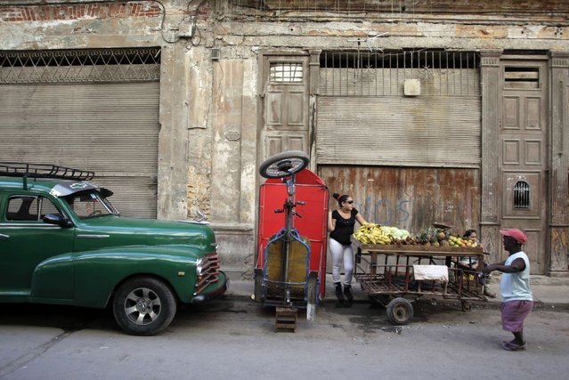 People stand next to a cart with fruit on a street in downtown Havana December 17, 2014. (Photo by Reuters/Stringer)
