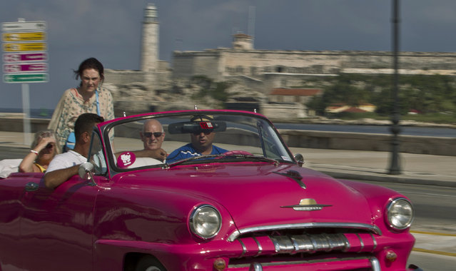 In this October 15, 2014 photo, tourists ride in a classic American car on the Malecon in Havana, Cuba. Those lucky enough to have a pre-revolutionary car can earn money legally by ferrying tourists – or Cubans celebrating weddings – along Havana's waterfront Malecon boulevard. (Photo by Franklin Reyes/AP Photo)