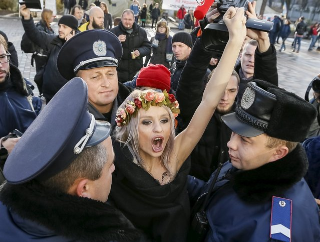 Ukrainian police detain an activist of women's rights group Femen as she protests against homophobia outside the parliament building in Kiev, Ukraine, November 12, 2015. Femen and gay rights activists are pushing parliament to adopt bills, including one that would ban discrimination in the workplace based on sexuality, which is included in a package of laws to liberalise Ukraine's visa regime with the EU. (Photo by Gleb Garanich/Reuters)