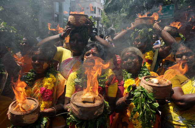 Indian members of the All India Anna Dravida Mennetra Kazhgam (AIADMK) organisation carry burning pots during a ritual offered for the health of Tamil Nadu Chief Minister Jayalalithaa Jayaram near the hospital where she is being treated in Chennai on October 18, 2016. A health bulletin from the hospital stated that the chief minister is being treated for a lung infection and would require a longer stay in hospital. (Photo by Arun Sankar/AFP Photo)