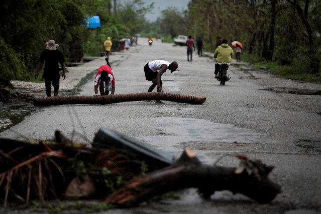 Residents carry a trunk to add it to a barricade set up to protest and demand aid for their neighborhood after Hurricane Matthew in Les Cayes, Haiti, October 21, 2016. (Photo by Andres Martinez Casares/Reuters)