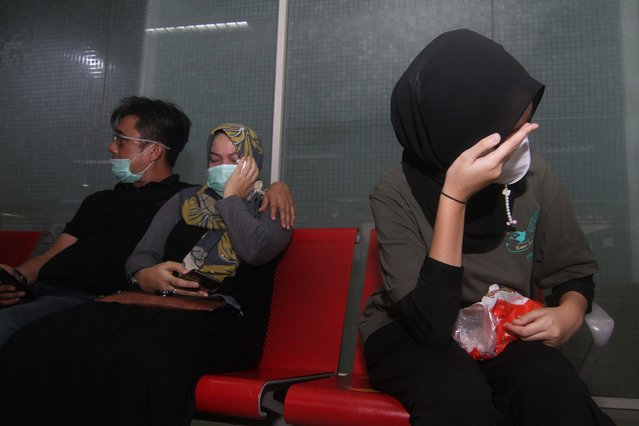 Relatives of passengers on board missing Sriwijaya Air flight SJY182 wait for news at the Supadio airport in Pontianak on Indonesia's Borneo island on January 9, 2021, after contact with the aircraft was lost shortly after take-off from Jakarta. (Photo by Louis Anderson/AFP Photo)