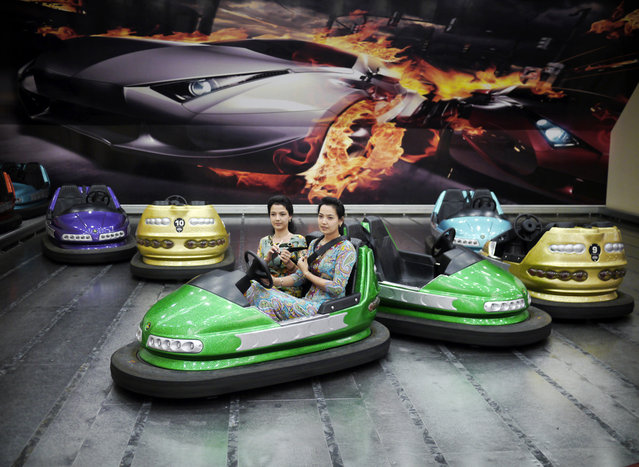 Two young women strap themselves into bumper cars in the Alem Entertainment Center. (Photo by Amos Chapple via The Atlantic)