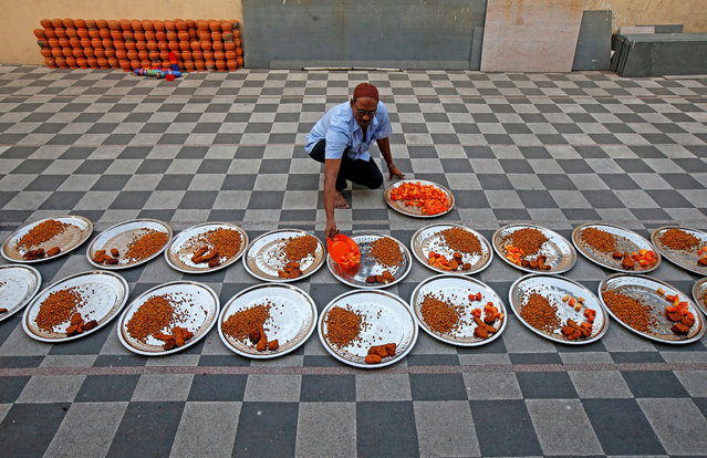 A man arranges Iftar (breaking fast) meals inside a mosque on the first day of the holy fasting month of Ramadan, in Kolkata, India May 17, 2018. (Photo by Rupak De Chowdhuri/Reuters)
