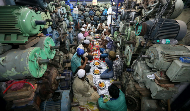 Indian Muslims gather for Iftar (breaking fast) meal inside a water pump shop in the Old quaters of Delhi, India, 02 June 2018. Muslims around the world celebrate the holy month of Ramadan by praying during the night time and abstaining from eating and drinking during the period between sunrise and sunset. Ramadan is the ninth month in the Islamic calendar and it is believed that the Koran's first verse was revealed during its last 10 nights. (Photo by Rajat Gupta/EPA/EFE)