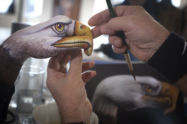 "Artist Guido Daniele ( R) works on one of his ""Handimals"" hand paintings at ""Top of the Rock"" at 30 Rockefeller Plaza in the Manhattan borough of New York January 15, 2015. The Italian-born artist paints hands to look like animals. (Photo by Carlo Allegri/Reuters)"