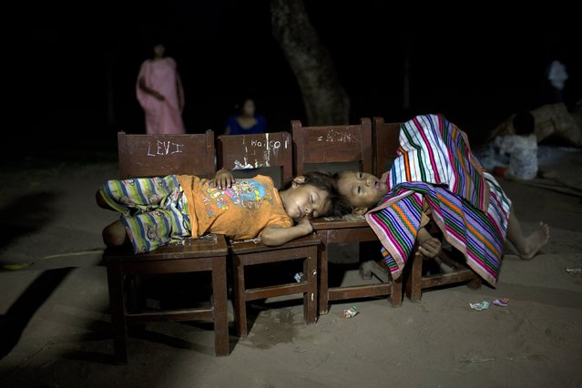 In this November 21, 2015 photo, boys rest during a Saturday night communal party in Potsoteni, an Ashaninka community in Peru's Junin region. An organization of Ashaninka representatives, known by its Spanish initials as CARE, says some 80 percent of children under age 5 suffer chronic malnutrition. That's reflected in abysmal education levels. Last year only 5 percent of students in the region passed an evaluation exam administered by CARE and the government. (Photo by Rodrigo Abd/AP Photo)