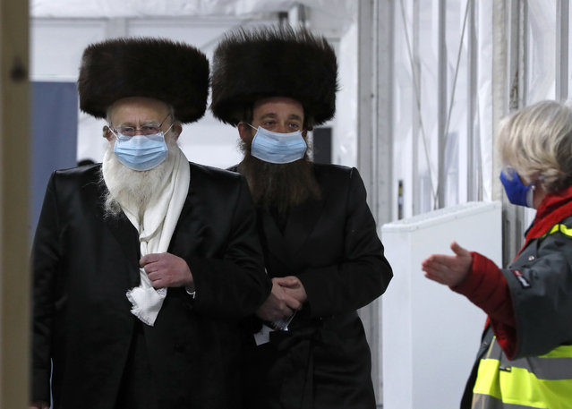 Two men from the Haredi Orthodox Jewish community arrive at an event to encourage vaccine uptake in the ultra-Orthodox community at the John Scott Vaccination Centre in London, Saturday, February 13, 2021. In hopes of breaking down barriers that sometimes isolate the Orthodox from wider society, community leaders organized the pop-up vaccination event for Saturday night to coincide with the end of Shabbat, the Jewish day of rest. (Photo by Frank Augstein/AP Photo)