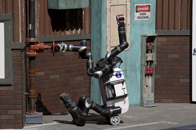 The Jet Propulsion Lab team's RoboSimian robot turns on a valve at a simulated disaster-response course during day one of the Defense Advanced Research Projects Agency (DARPA) Robotics Challenge finals in Pomona, California, June 5, 2015. (Photo by David McNew/Reuters)