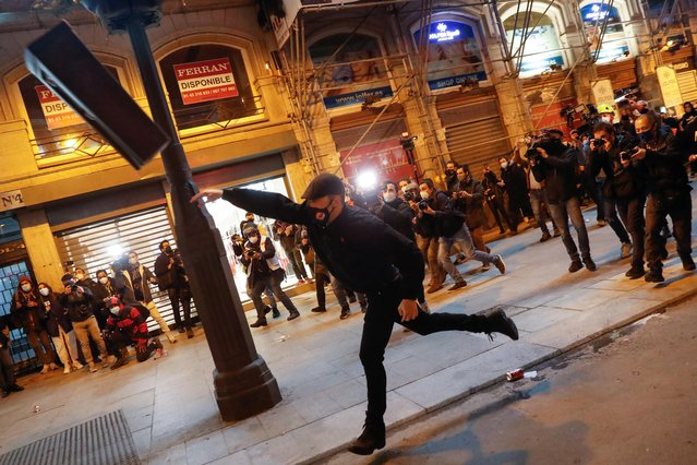 A demonstrator throws a bin as supporters of Catalan rapper Pablo Hasel protest against his arrest in Madrid, Spain, February 17, 2021. (Photo by Susana Vera/Reuters)