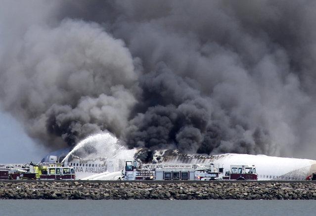 Fire crews work the crash site of Asiana Flight 214 at San Francisco International Airport in San Francisco, Saturday, July 6, 2013. (Photo by  John Green/AP Photo/Bay Area News Group)