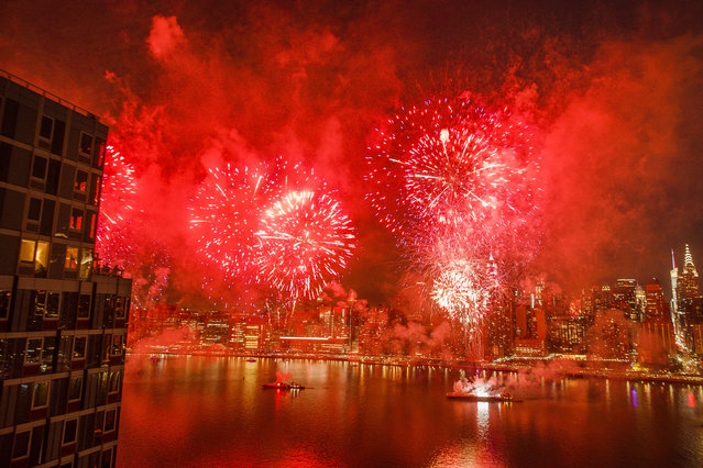 With the New York City skyline in the background, fireworks explode during an Independence Day show over the East River, Wednesday, July 4, 2018, in New York. (Photo by Andres Kudacki/AP Photo)