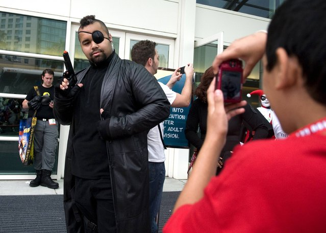 Edward Gonzalez (R), 12, takes a photo of Chuck Roquemore, who's dressed as Nick Fury from The Avengers, outside the exhibit halls at Comic-Con International in San Diego, California July 12, 2012. (Photo by Mario Anzuoni/Reuters)