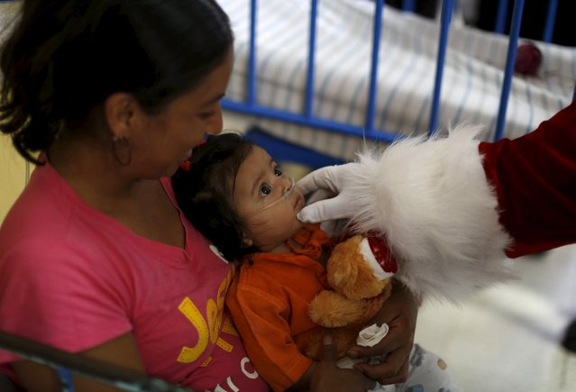A man dressed as Santa Claus touches a baby at the San Juan de Dios Hospital in Guatemala City, December 16, 2015. The hospital organises the event annually where Santa Claus distributes gifts to children receiving medical attention. (Photo by Jorge Dan Lopez/Reuters)