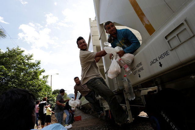 "Volunteers from a group called ""Las Patronas"" (The bosses), a charitable organization that feeds Central American immigrants who travel atop a freight train known as ""La Bestia"", pass food and water to immigrants on their way to the border with the United States, at Amatlan de los Reyes, in Veracruz state, Mexico October 22, 2016. (Photo by Daniel Becerril/Reuters)"