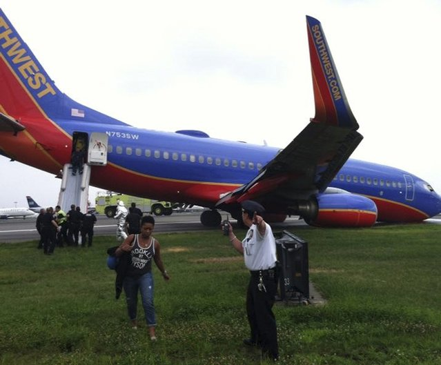 A Southwest Airlines plane sits on the tarmac as passengers disembark at LaGuardia airport in New York, July 22, 2013, in this photo courtesy of @mattjfriedman and Frank Ferramosca. The Southwest Airlines plane flying from Nashville to New York City landed without its nose gear at LaGuardia airport on Monday but no one was hurt, the Federal Aviation Administration (FAA) said. (Photo by @mattjfriedman/Frank Ferramosca/Handout via Reuters)