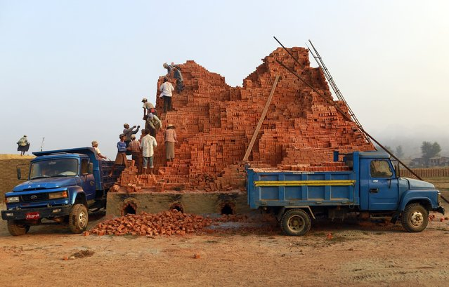 Workers move bricks at a brick kiln on the outskirts of Yangon February 1, 2015. (Photo by Soe Zeya Tun/Reuters)