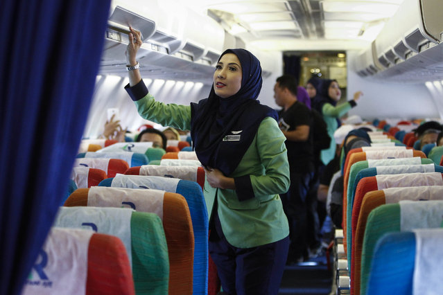 In this December 22, 2015, photo, a Rayani Air flight crew checks the luggage compartment before departure at the Sultan Ismail Petra Airport in Kelantan, Malaysia. (Photo by Joshua Paul/AP Photo)