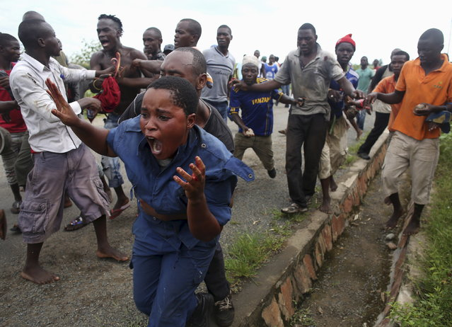 Protesters attack a female police officer accused of shooting a protestor in the Buterere neighbourhood of Bujumbura, Burundi, May 12, 2015. Protestors opposed to the president's decision to run for a third term chased, beat and stoned the woman, who was later handed back to police. (Photo by Goran Tomasevic/Reuters)