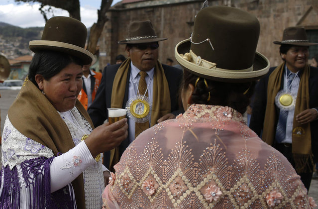 """In this Sunday, August 5, 2018 photo, """"cholas"""" share a toast during a pause in the religious procession honoring Our Lady of Coapacabana in Cuzco, Peru. It is customary that organizers offer free food and drink for celebrants, along with a small fee for the dancers and musicians. According to the steward of this year's celebrations in Cuszo, expenditures totaled 9,000 U.S. dollars. (Photo by Martin Mejia/AP Photo)"""