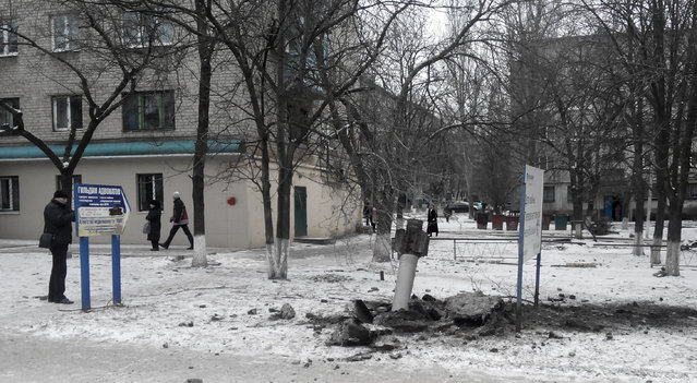 A resident passes by an unexploded rocket in a living area in Kramatorsk, Ukraine, Tuesday, February10, 2015.  (Photo by AP Photo)