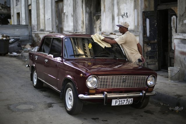 Reynaldo Perez cleans his Lada 1200 built in 1980 on a street in downtown Havana February 7, 2015. The former Soviet Union began exporting its cheaply built models to Cuba in the 1970s until production began to peter out a decade ago. (Photo by Enrique De La Osa/Reuters)