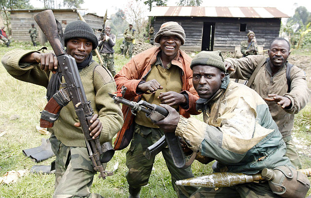 Congolese armed forces (FARDC) soldiers pose for a photograph as they celebrate winning a Kibati village during their battle with M23 rebels outside Goma August 30, 2013. Democratic Republic of Congo's M23 rebels suspended fighting and withdrew from the frontline on Friday to allow an independent investigation into shelling that hit neighbouring Rwanda, its leader said. (Photo by Thomas Mukoya/Reuters)