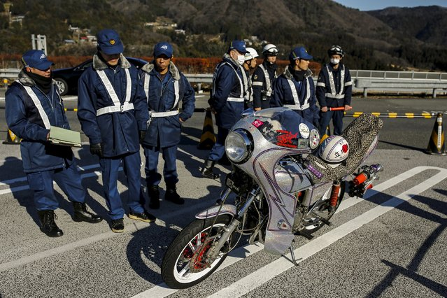Policemen inspect a customised Bousouzoku style motorcycle at the Dangouzaka rest stop in Yamanashi, west of Tokyo, Japan, January 3, 2016. (Photo by Thomas Peter/Reuters)