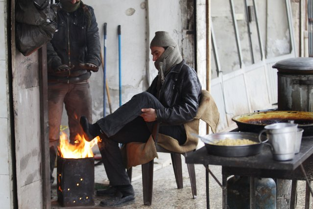 A street vendor warms his foot around a fire during cold weather in the rebel-controlled area of Maaret al-Numan town in Idlib province, Syria, January 4, 2016. REUTERS/Khalil Ashawi