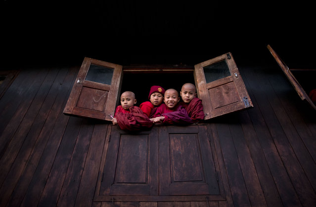 In this January 11, 2015 photo, ethnic Ta'ang novice Buddhist monks peep out of a monastery window to watch Ta'ang National Liberation army (TNLA) leaders who gathered in Mar Wong, a village in northern Shan state, Myanmar to celebrate the 52nd anniversary of their insurrection. (Photo by Gemunu Amarasinghe/AP Photo)