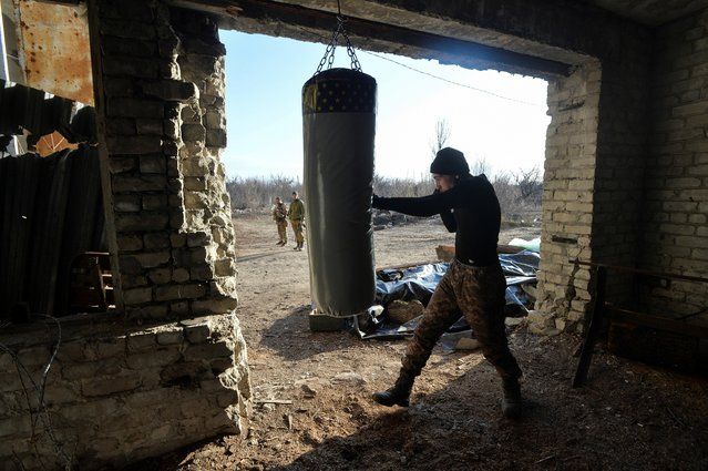 A service member of the Ukrainian armed forces practices boxing at fighting positions on the line of separation from pro-Russian rebels near Donetsk, Ukraine on April 10, 2021. (Photo by Oleksandr Klymenko/Reuters)