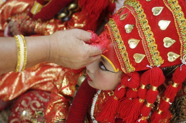 A Nepalese girl wearing a traditional attire receives a red tika on her forehead during the Kumari Puja, a mass worship, at Hanuman Dhoka in Durbar Square in Kathmandu, September 17, 2013. (Photo by Bikash Dware/Reuters)