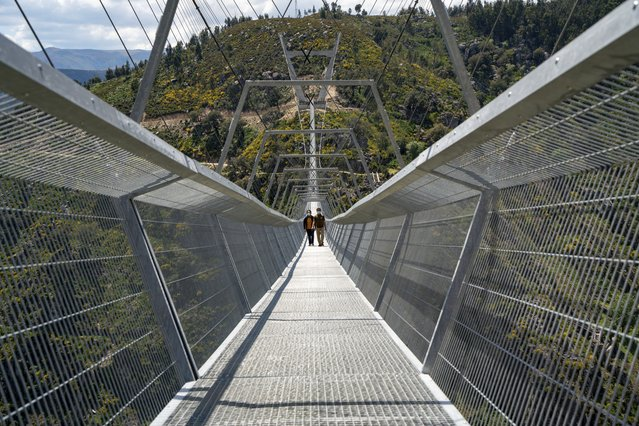 People walk across a narrow footbridge suspended across a river canyon, which claims to be the world's longest pedestrian bridge, in Arouca, northern Portugal, Sunday, May 2, 2021. (Photo by Sergio Azenha/AP Photo)