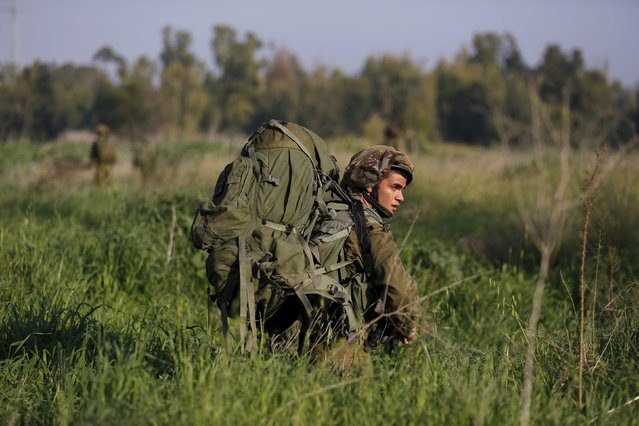 An Israeli soldier walks in a field during military activity across from the Israeli-Gaza border in southern Israel January 13, 201. (Photo by Amir Cohen/Reuters)