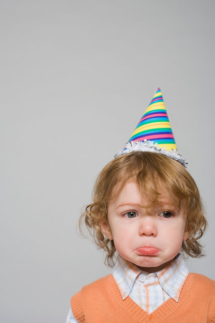 Sad boy in a party hat. (Photo by Alamy Stock Photo)