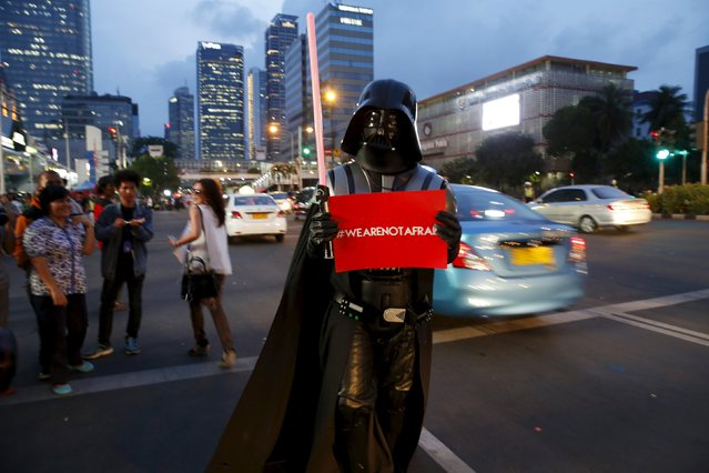 A man wearing Darth Vader costume holds a placard as he stands on Thamrin street near the scene of Thursday's gun and bomb attack, in Jakarta, Indonesia January 15, 2016. Indonesian police arrested three suspected militants in a pre-dawn raid and hunted down others across the country on Friday, a day after an attack by Islamic State suicide bombers and gunmen in the heart of the Southeast Asian nation's capital. (Photo by Reuters/Beawiharta)
