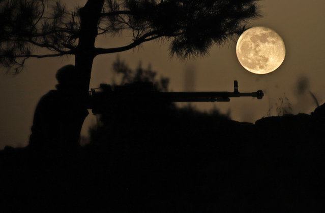 April's Pink Super Moon rises behind a fighter of the Turkish-backed Free Syrian Army in the rebel-held southern countryside of Syria's northwestern province of Idlib on April 28, 2021. (Photo by Abdulaziz Ketaz/AFP Photo)