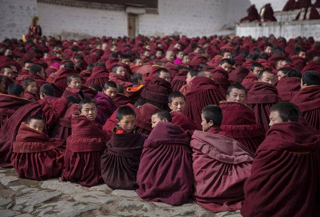 Young Tibetan Buddhist monks take part in a special prayer during Monlam or the Great Prayer rituals on March 5, 2015 at the Labrang Monastery, Xiahe County, Amdo, Tibetan Autonomous Prefecture, Gansu Province, China. (Photo by Kevin Frayer/Getty Images)