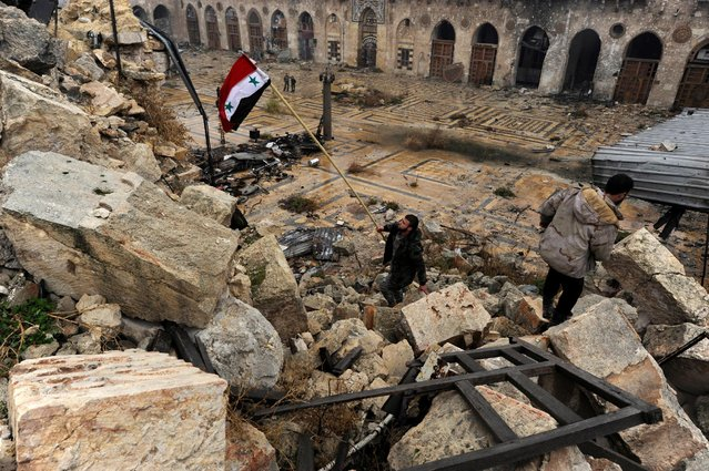 A member of forces loyal to Syria's President Bashar al-Assad attempts to erect the Syrian national flag inside the Umayyad mosque, in the government-controlled area of Aleppo, during a media tour, Syria December 13, 2016. (Photo by Omar Sanadiki/Reuters)
