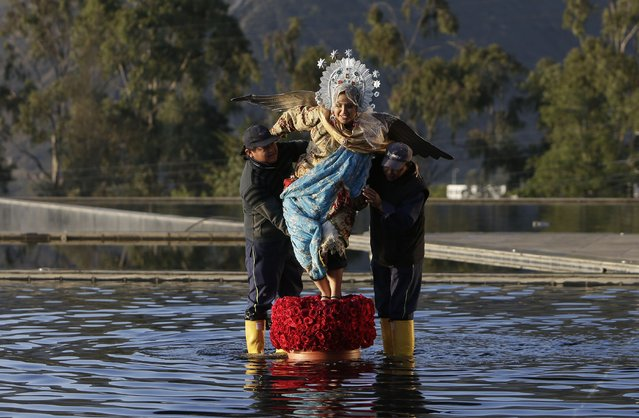 A woman wearing a costume of the Virgin Mary is helped by two men to her position as part of the arrangements and actors welcoming the heads of state to the IV Summit of the Community of Latin American and Caribbean States, CELAC, in Quito, Ecuador, Wednesday, January 27, 2016. The Dominican Republic will take over the rotating presidency of the CELAC from Ecuador, during the summit. (Photo by Dolores Ochoa/AP Photo)