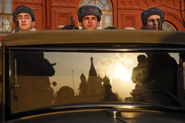 Russian soldiers dressed in Red Army World War II uniforms sit in the back of a truck as the St. Basil's Cathedral is reflected in the windshield prior to the start of the November 7 parade in Red Square, with St. Basil Cathedral and thew Spasskaya Tower in the background, in Moscow, Russia, Wednesday, Nov. 7, 2018. The event marked the 77th anniversary of a World War II historic parade in Red Square and honored the participants in the Nov. 7, 1941 parade who headed directly to the front lines to defend Moscow from the Nazi forces. (Photo by Alexander Zemlianichenko/AP Photo)