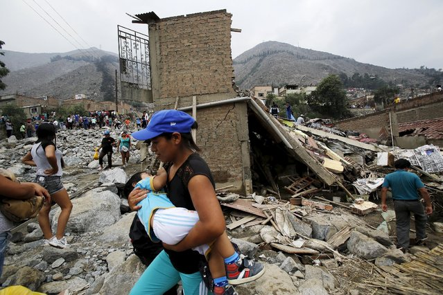 A woman carries a baby as she walks past debris of houses after a massive landslide in Chosica, March 24, 2015. (Photo by Mariana Bazo/Reuters)
