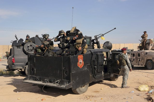 Iraqi security forces prepare to attack Islamic State extremist positions during clashes in Tikrit, 130 kilometers (80 miles) north of Baghdad, Iraq, Friday, March 27, 2015. On the ground, the Iraqi troops pressed their push in the city on Friday as fighter planes pounded IS targets from above. Militants holed up in the center of Tikrit fired mortars at the military, slowing its progress despite the new aerial campaign. (Photo by Khalid Mohammed/AP Photo)