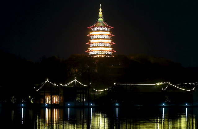Leifeng Pagoda is seen behind the West Lake before Earth Hour in Hangzhou, Zhejiang province, March 28, 2015. (Photo by Chance Chan/Reuters)