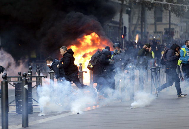People run away from a burning car during clashes, Saturday, December 8, 2018 in Marseille, southern France. The grassroots movement began as resistance against a rise in taxes for diesel and gasoline, but quickly expanded to encompass frustration at stagnant incomes and the growing cost of living. (Photo by Claude Paris/AP Photo)