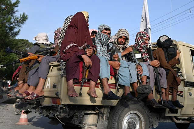 Taliban fighters in a vehicle patrol the streets of Kabul on August 23, 2021 as in the capital, the Taliban have enforced some sense of calm in a city long marred by violent crime, with their armed forces patrolling the streets and manning checkpoints. (Photo by Wakil Kohsar/AFP Photo)