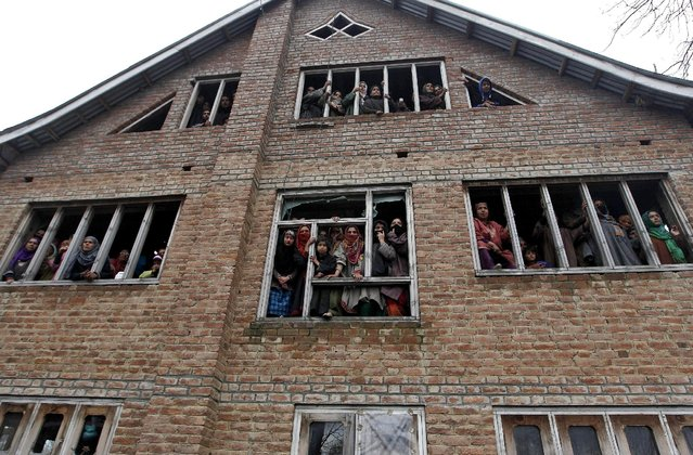 Kashmiri people watch the funeral procession of Mushatq Ahmad Wani, an Indian policeman, from the windows of a house during his funeral in Arigam, south of Srinagar April 6, 2015. (Photo by Danish Ismail/Reuters)